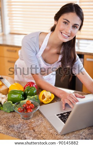 Portrait of a young woman looking for a recipe on the internet in her kitchen