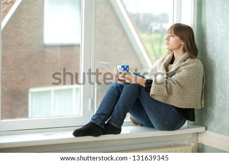 Portrait of a young woman looking out window - stock photo