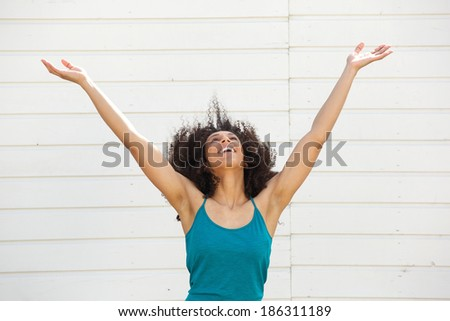 Portrait of a young woman looking up with arms outstretched - stock photo