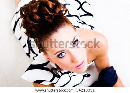 Portrait of a young woman lying. Her hair is styled in an updo and she is wearing a black and white dress, gloves and high heels. Vertical shot. Isolated on white. - stock photo