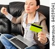 Portrait of a young woman lying on the couch and shopping from the internet using a credit card - stock photo