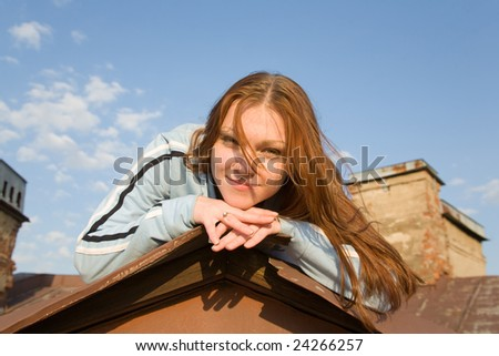 portrait of a young woman lying on the roof peak