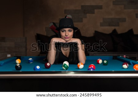 Portrait Of A Young Woman Lying On The Table And Playing Billiards - stock photo