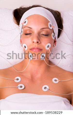 Portrait of a young woman lying  with electrodes on her face - stock photo