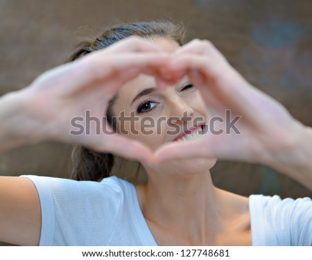 Portrait of a young woman making a heart shape sign with her hands, studio shot