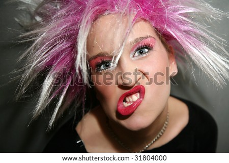 Portrait of a young woman, making a silly face, with pink wig and pink make-up - stock photo