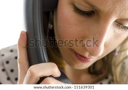 Portrait of a young woman on a phone looking down. - stock photo