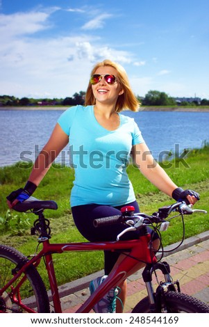 Portrait of a young woman on bicycle, outdoor shoot