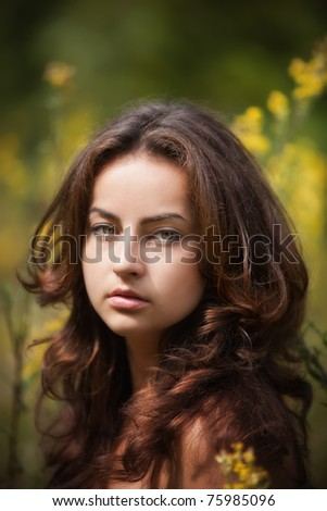 Portrait of a young woman on blured flowers field background - stock photo