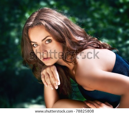 Portrait of a young woman on blured forest background - stock photo