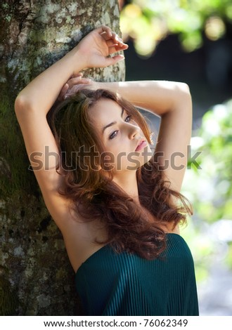 Portrait of a young woman on forest background - stock photo
