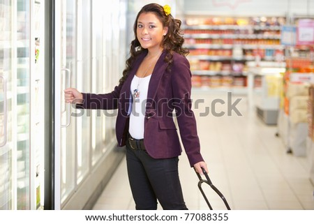 Portrait of a young woman opening refrigerator in the supermarket - stock photo