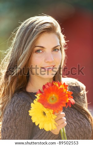 Portrait of a young woman outdoor in autumn holding beautiful flowers. - stock photo