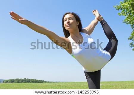 Portrait of a Young Woman performing Yoga outdoors in the country side - stock photo