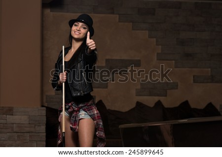Portrait Of A Young Woman Playing Billiards - stock photo