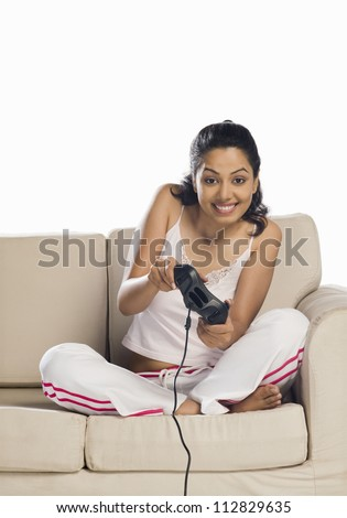 Portrait of a young woman playing video game - stock photo