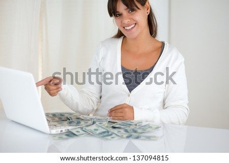 Portrait of a young woman pointing laptop screen with cash money while is smiling and looking at you - stock photo