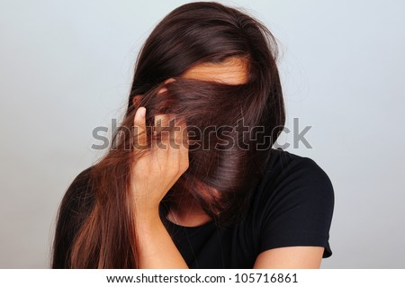 Portrait of a young woman pulling her long brown hair across her face. Female is unrecognizable.