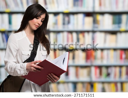 Portrait of a young woman reading a book - stock photo