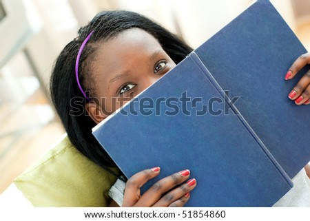 Portrait of a young woman reading a book lying on a sofa - stock photo