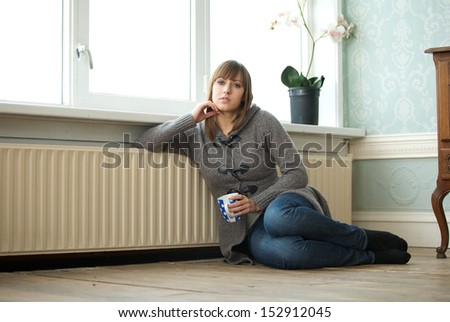 Portrait of a young woman relaxing at home with cup of coffee  - stock photo