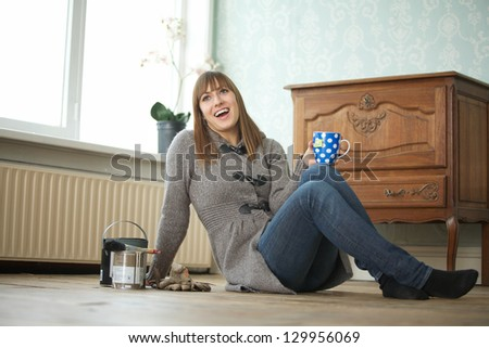 Portrait of a young woman relaxing with a cup of tea - stock photo