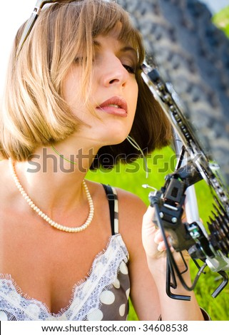 Portrait of a young woman repairing a bike - stock photo