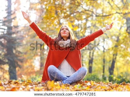 Portrait of a young woman resting in a park with arms outstretched, she sitting on on the leaves