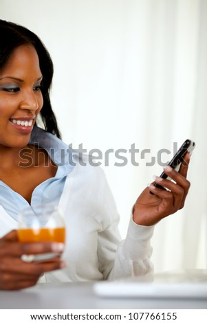 Portrait of a young woman sending a message by cellphone at home indoor - stock photo