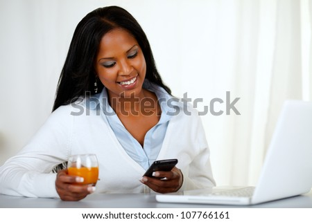 Portrait of a young woman sending a message by the mobile at home indoor - stock photo