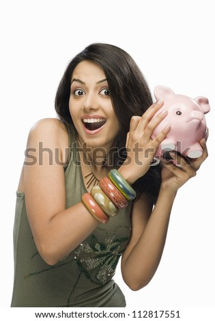 Portrait of a young woman shaking a piggy bank - stock photo