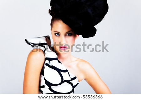 Portrait of a young woman. She is wearing a large hat and a black and white dress with a bow on the shoulder. Horizontal shot. - stock photo