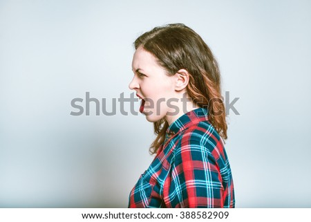 Portrait of a young woman shouting angry, isolated on a gray background