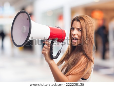 portrait of a young woman shouting with a megaphone - stock photo