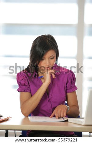 Portrait of a young woman sitting at a desk with documents and a laptop computer - stock photo