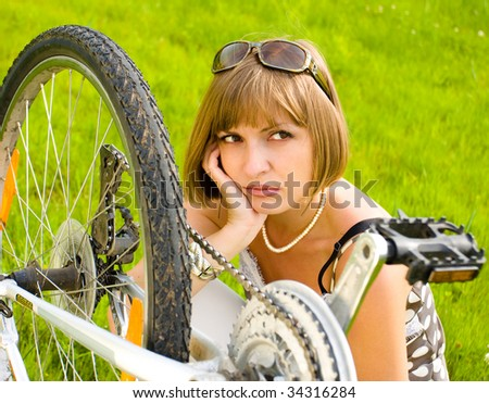 Portrait of a young woman sitting beside an upturned bike - stock photo