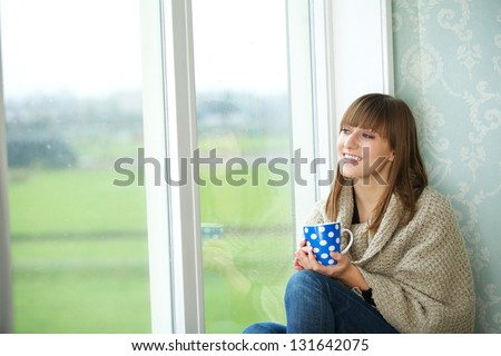 Portrait of a young woman sitting by window with cup of tea - stock photo