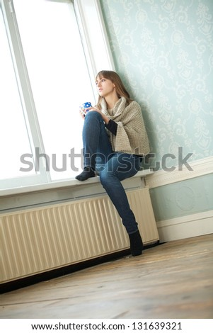 Portrait of a young woman sitting in empty room - stock photo