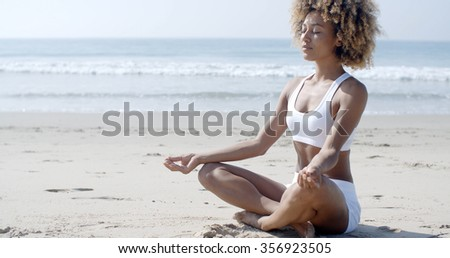 Portrait of a young woman sitting in yoga pose at the beach - stock photo
