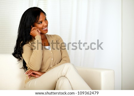 Portrait of a young woman sitting on a sofa and talking on cellphone at home indoor - stock photo