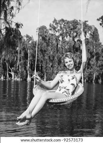 Portrait of a young woman sitting on a swing at the lakeside and smiling - stock photo