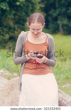 Portrait of a young woman sitting on the stone and holding mobile phone - stock photo