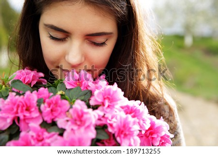 Portrait of a young woman smelling pink flowers - stock photo