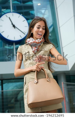 Portrait of a young woman smiling and looking at watch outdoors - stock photo