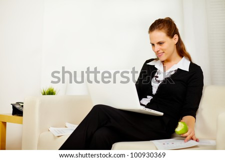 Portrait of a young woman smiling and working at sofa and eating a apple - stock photo