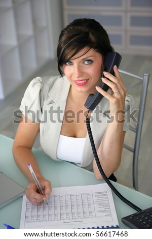 Portrait of a young woman smiling on phone writing on a document