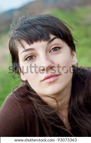 Portrait of a young woman smiling outdoors - stock photo