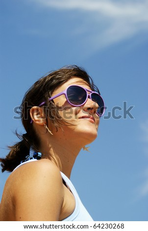 Portrait of a young woman smiling that wears sunglasses and looking somewhere far away - stock photo