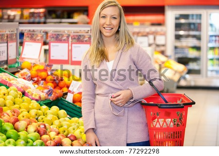 Portrait of a young woman smiling while buying fruits in the supermarket - stock photo
