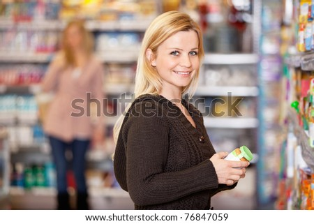 Portrait of a young woman smiling while shopping in the supermarket - stock photo